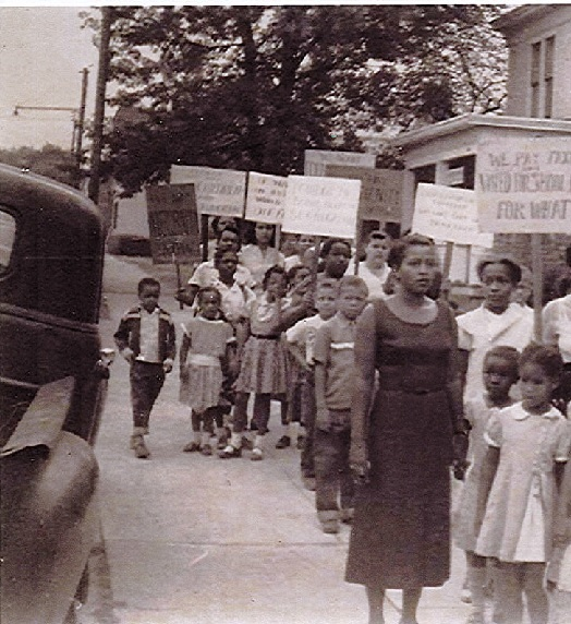 black and white photo of the mothers and children marching with signs demanding integration